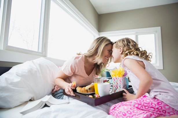 daughter-bringing-breakfast-to-mother-in-bed